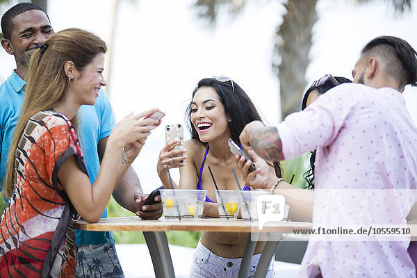 Friends using cell phone at table outdoors