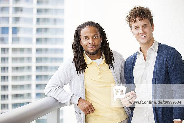Businessmen using cell phone on urban balcony
