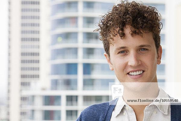 Caucasian man smiling on urban balcony