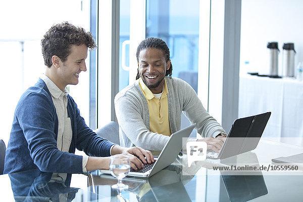 Businessmen working on laptops in office meeting