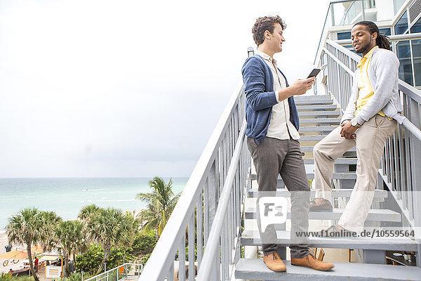 Businessmen talking on steps over urban beach