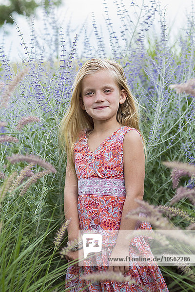 Caucasian girl smiling in tall grass
