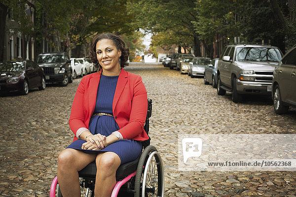 Kopfsteinpflaster Frau lächeln Straße Behinderung Rollstuhl