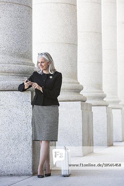 Handy benutzen Europäer Geschäftsfrau unterhalb Säule