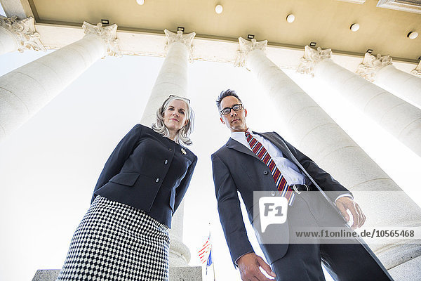 Low angle view of business people under columns