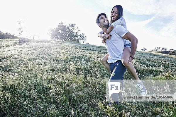 Mann Freundin tragen Feld huckepack