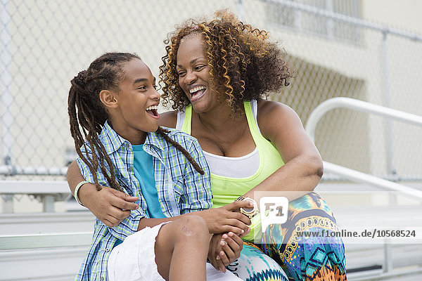 Mixed race mother and son hugging on bleachers