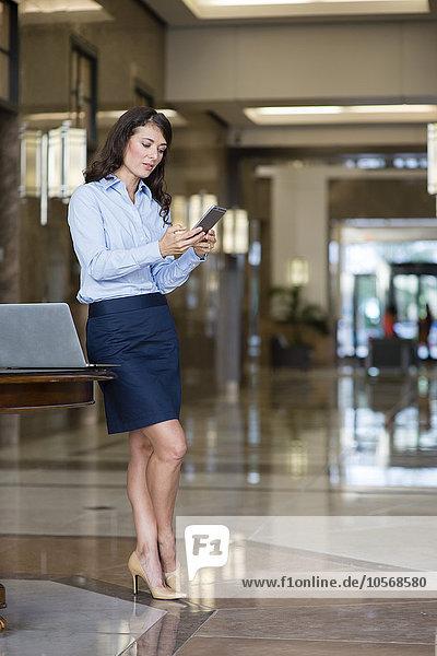 Handy benutzen Eingangshalle Europäer Geschäftsfrau