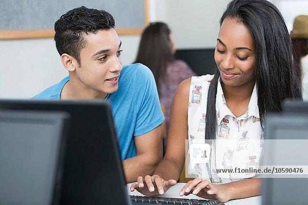 Zwei Teenager  die in der Highschool-Klasse am Computer tippen.