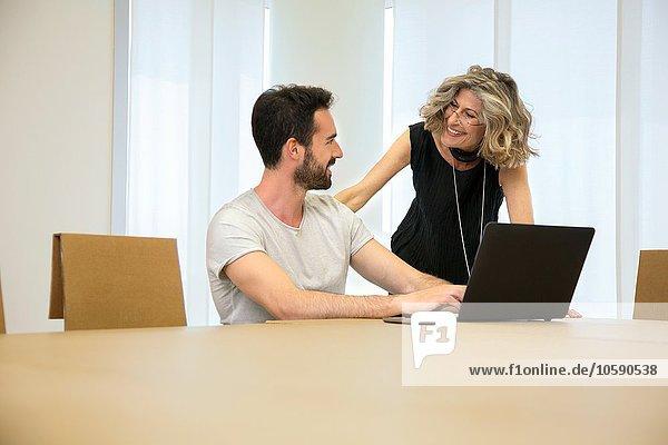 Geschäftsfrau im Gespräch mit Designer im Büro