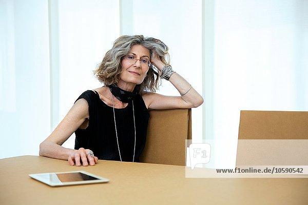 Porträt einer Senior-Designerin am Vorstandstisch