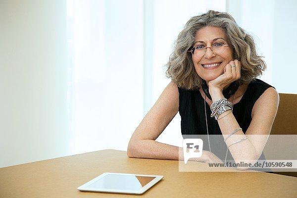 Portrait einer Senior-Designerin mit digitalem Tablett am Konferenztisch