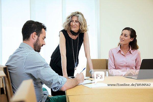 Drei Designer beim Brainstorming am Vorstandstisch