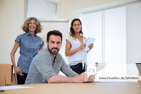 Porträt eines jungen Geschäftsmannes und zweier Amtskolleginnen