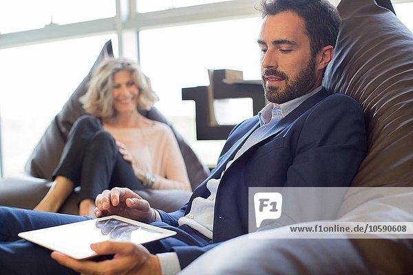 Zwei Designer entspannt auf Sitzsackstühlen im Büro