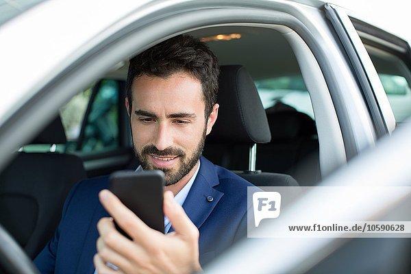 Jungunternehmer beim Lesen von Smartphone-Texten im Auto