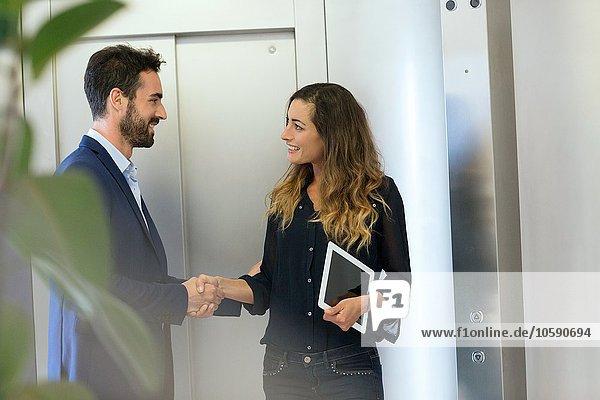 Junger Geschäftsmann und Frau beim Händeschütteln am Aufzug