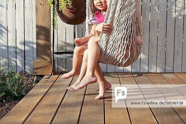 Mädchen sitzen in der Hängematte auf der Veranda