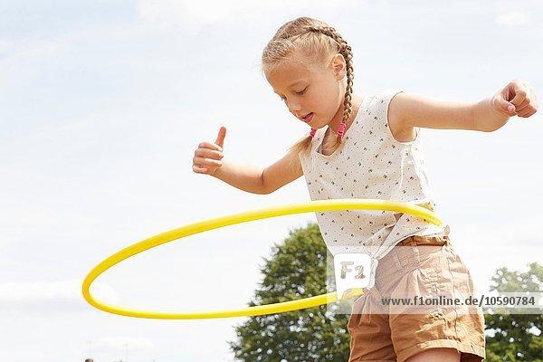 Niederwinkelansicht des Mädchens mit Hula-Reifen  Arme offen nach unten gerichtet
