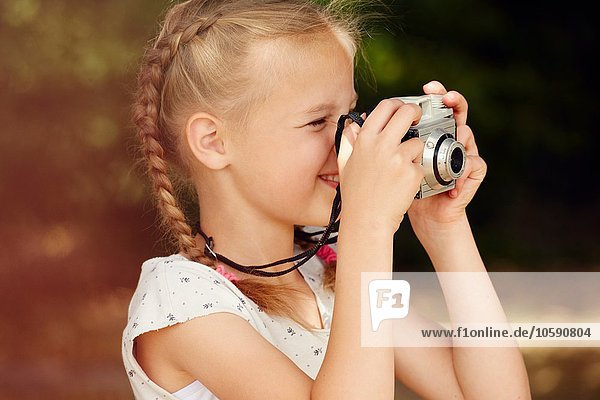 Head and shoulder side view of girl using film camera