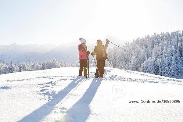 Seniorenpaar auf verschneiter Landschaft mit wegblickenden Wanderstöcken  Sattelbergalm  Tirol  Österreich