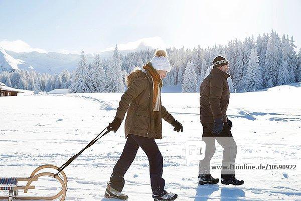 Seitenansicht des Seniorenpaares auf schneebedecktem Schlitten  Sattelbergalm  Tirol  Österreich