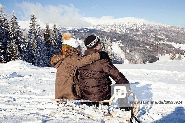 Schneebedeckte Berge und Rückansicht des Seniorenpaares auf dem Schlitten sitzend  Sattelbergalm  Tirol  Österreich