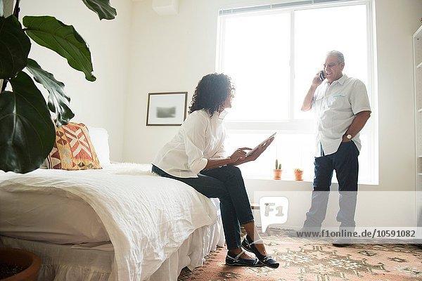 Reife Frau auf dem Bett mit digitalem Tablett  während der Ehemann auf dem Smartphone spricht