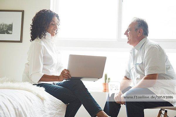 Älteres Ehepaar mit Laptop im Schlafzimmer