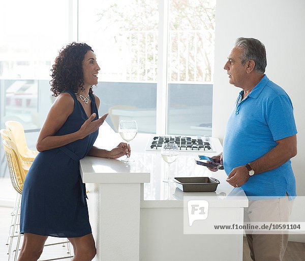 Senior man and wife chatting over kitchen counter