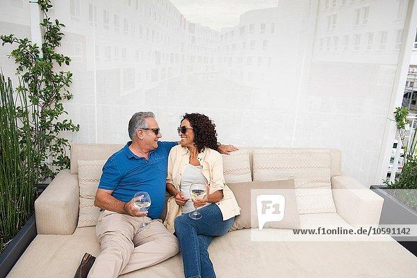 Senior Mann und Frau sitzen auf einem Sofa auf der Terrasse.