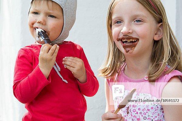 Weibliches Kleinkind und Schwester essen unordentlich Schokoladeneis Weibliches Kleinkind und Schwester essen unordentlich Schokoladeneis