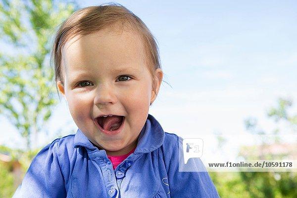 Portrait of cute female toddler in garden