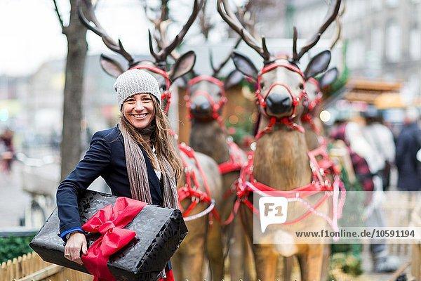 Portrait einer reifen Frau mit Weihnachtsgeschenk vor Rentierausstellung  Kopenhagen  Dänemark