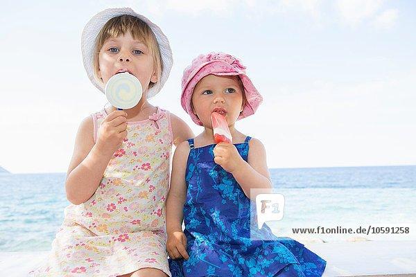 Weibliches Kleinkind und Schwester tragen Sonnenhüte und essen Eis am Strand