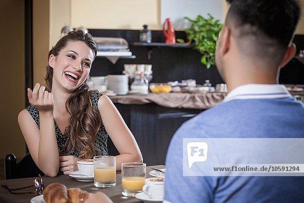Junges Paar lacht beim Frühstück im Speisesaal des Hotels