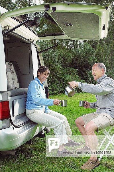 Seniorenpaar neben Wohnmobil sitzend  Tee gießend