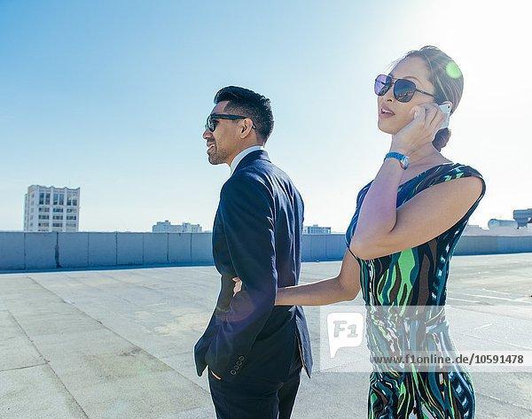 Geschäftsmann mit Geschäftsfrau mit Smartphone auf der Dachterrasse  Los Angeles  Kalifornien  USA