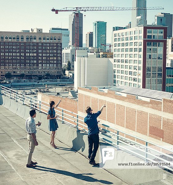 Geschäftsleute  die auf Gebäude auf der Dachterrasse schauen und zeigen  Los Angeles  Kalifornien  USA