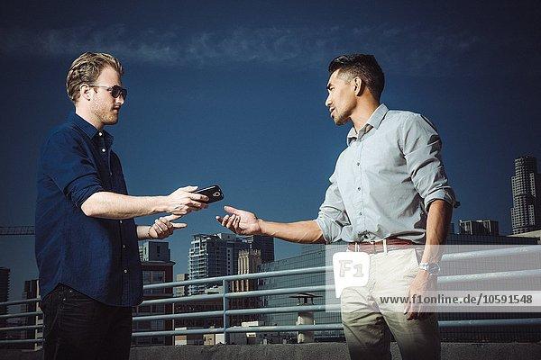 Geschäftsmann gibt Smartphone an Mann auf der Dachterrasse  Los Angeles  Kalifornien  USA