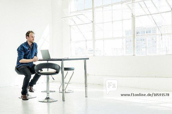 Geschäftsmann bei der Arbeit am Laptop am Bürofenster