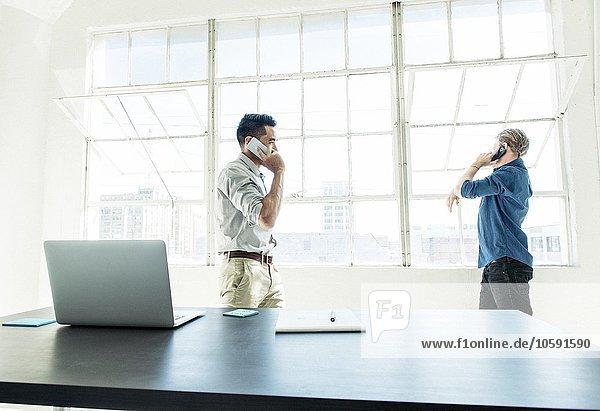 Geschäftsleute beim Sprechen auf dem Smartphone durch das Bürofenster