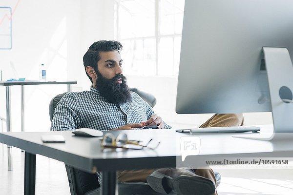 Bärtiger Geschäftsmann vor dem Computer sitzend