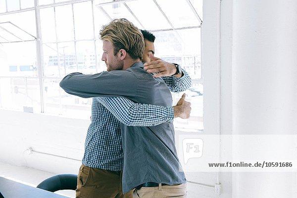 Geschäftsleute umarmen sich beim Treffen