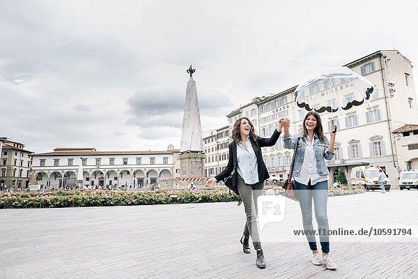 Lesbisches Pärchen mit Regenschirm und lächelnden Händen  Piazza Santa Maria Novella  Florenz  Toskana  Italien