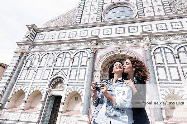 Flachwinkelaufnahme eines lesbischen Paares  das eine Digitalkamera auf der Wange vor der Kirche hält  Piazza Santa Maria Novella  Florenz  Toskana  Italien
