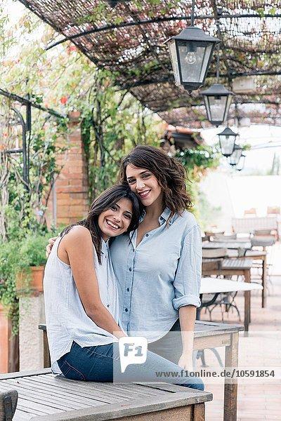 Lesbisches Paar in pflanzenbedecktem Bogenkopf auf Brustumarmung  Blick auf Kamera lächelnd  Florenz  Toskana  Italien