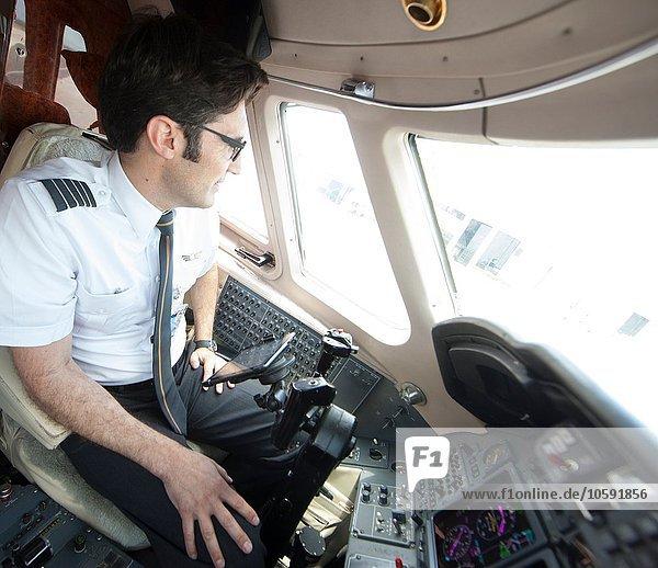 Männlicher Pilot schaut durch das Cockpitfenster des Privatjets