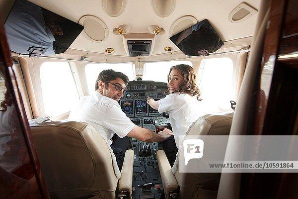 Rückansicht des männlichen Piloten mit Hand auf dem Knie der Frau im Cockpit des Privatjets