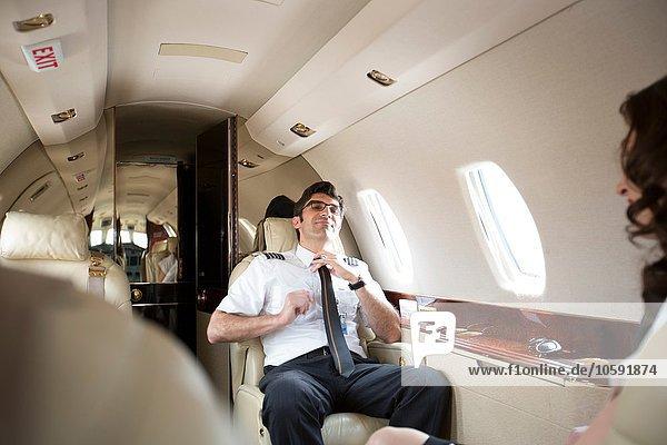 Männlicher Pilot  der die Krawatte in der Kabine des Privatjets löst